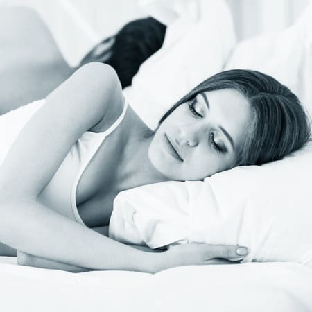 woman sleeping. Too little or too much sleep can cause migraines just like gluten