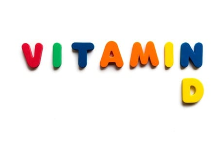 Vitamin D in colorful block letters- vitamin deficiency or toxicity can cause symptoms