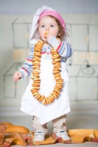 child with bread necklace