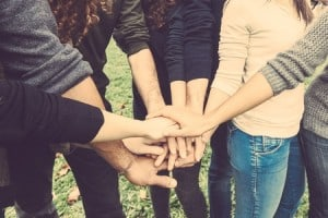 multiple people standing in a circle clasping hands. One of the upsides of a celiac diagnosis- community