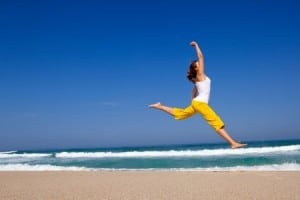 A woman doing a split leap, jumping for joy on the beach. One of the positive aspects of celiac disease is getting an actual diagnosis. You are no longer sick
