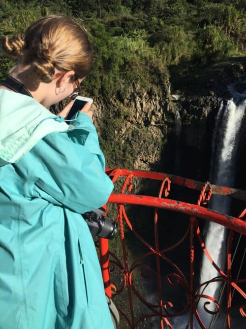 girl taking a picture of waterfall Gluten Free in Ecuador