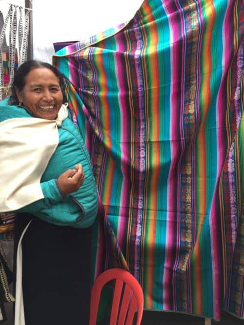 indigenous Ecuadorian woman holding a blanket in a market