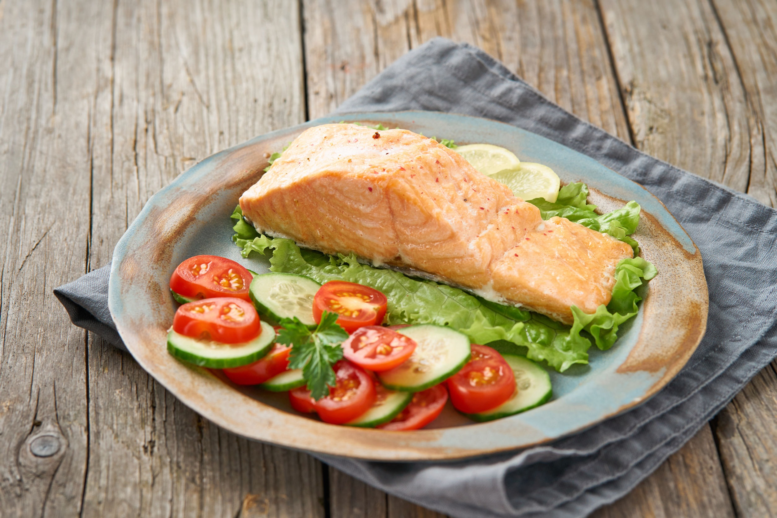 Salmon on a plate with tomatoes and cucumber. All are ok on a low fodmap and gluten free diet