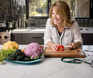 Dr. Amy Burkhart in kitchen, laughing with food and stethescope