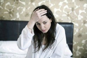 pots syndrome can cause headaches and flu-like symptoms. image is of a woman holding her head