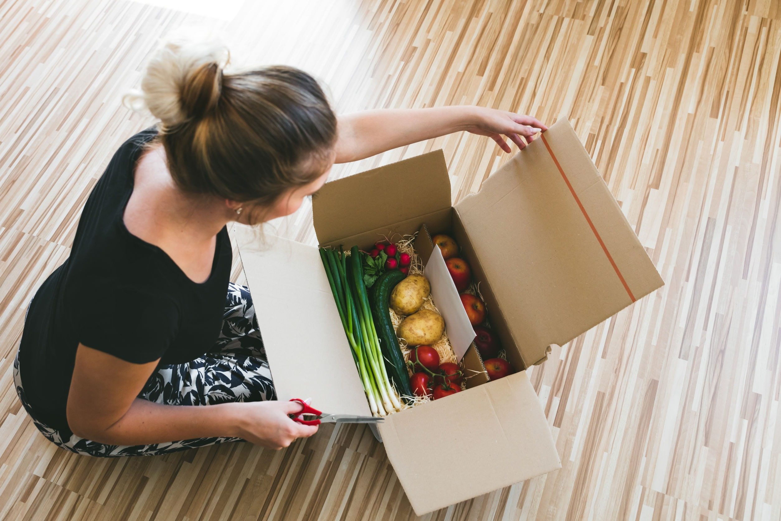 Woman opening a box of groceries that were ordered online. Online food resources for special diets are important. Gluten free bakery and keto bakery options can be bought online as can many special diet items