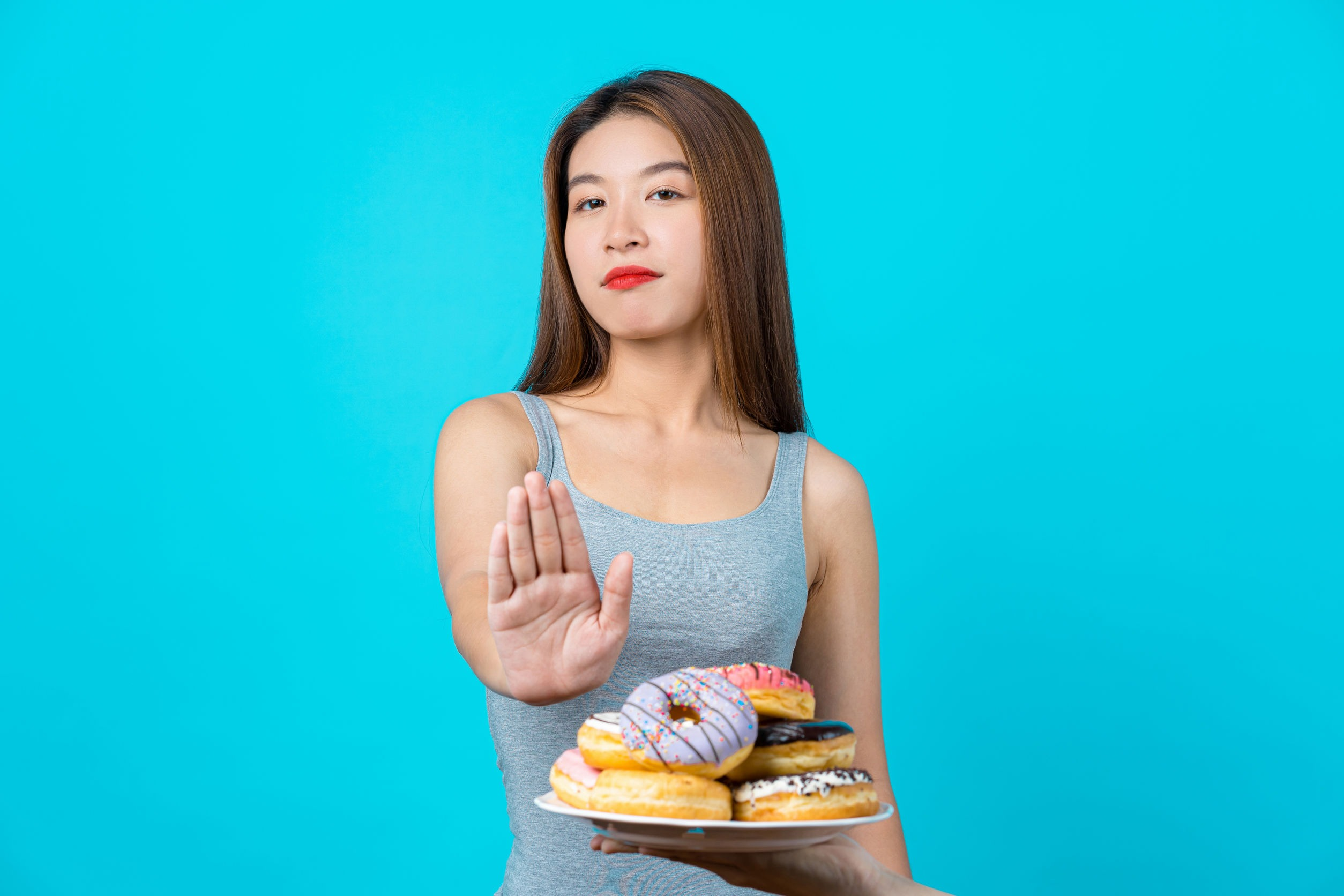 Woman on a sucrose intolerance diet putting her hand out to say no to donuts. She is on a low sucrose diet