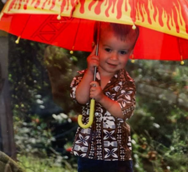 young boy holding an umbrella and smiling