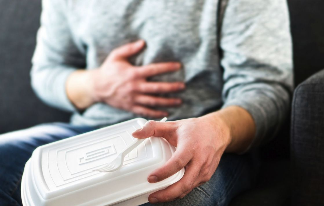 """Man holding his stomach and an empty """" to-go"""" food box. Food can trigger mast cell activation syndrome / MCAS and cause IBS symptoms"""