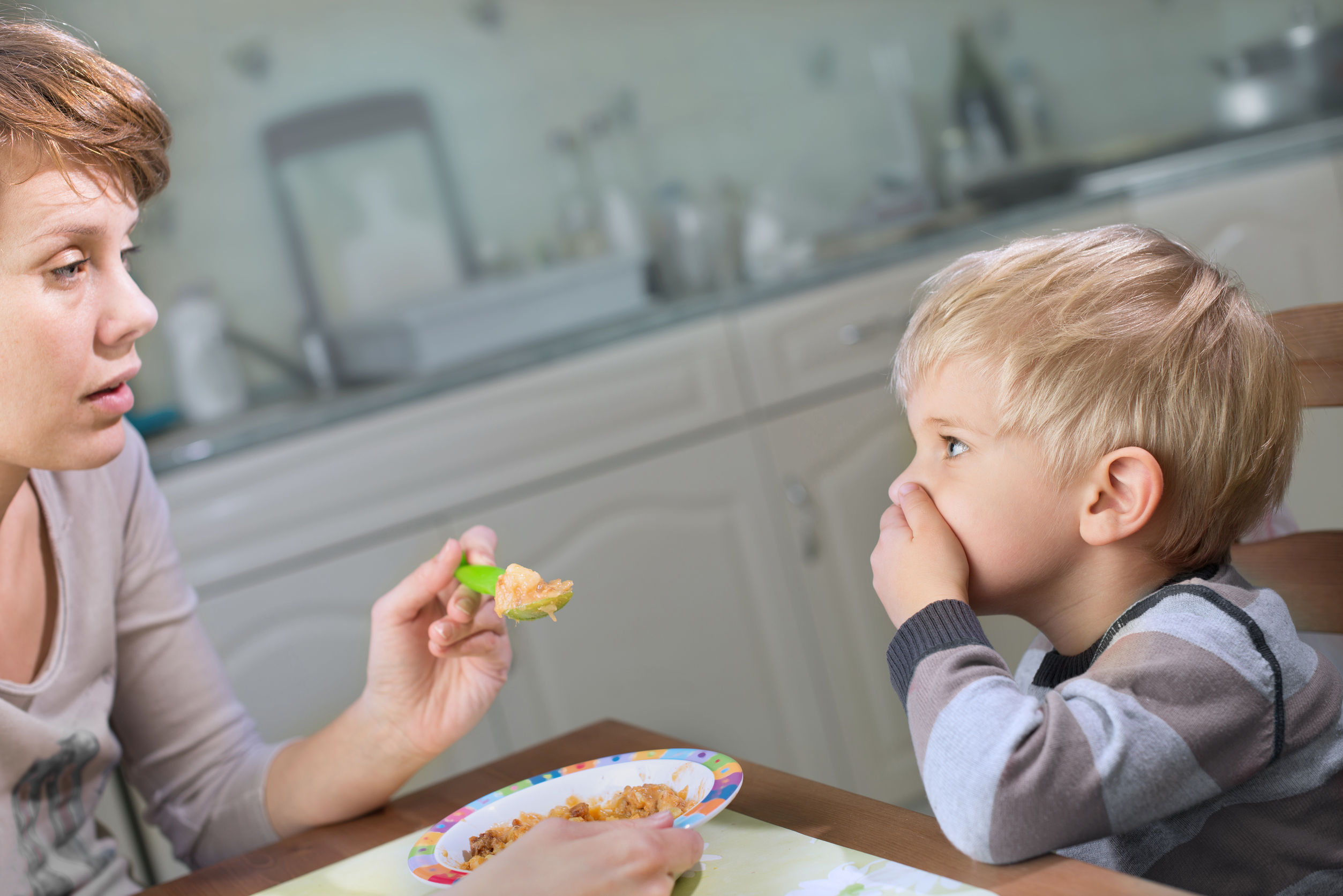 ARFID is not the same as a picky eater. This is a picture of a mom trying to feed a small boy but he is covering his mouth and refusing food.